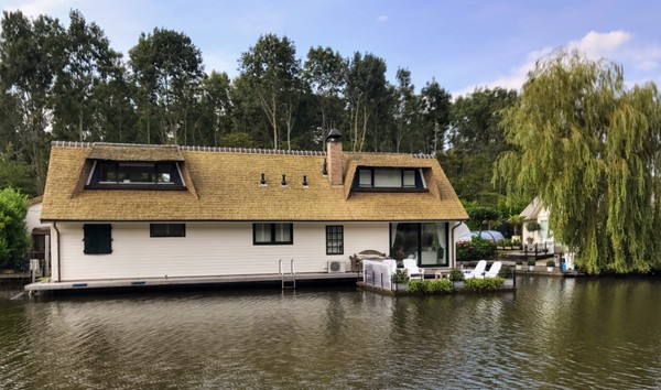 A brick and thatch houseboat on a Flavoland  canal