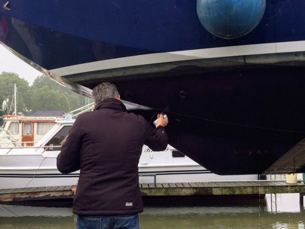 Surveyor Tom carefully examines the hull