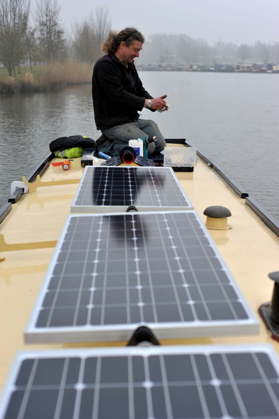 Tim Davis fitting solar panels on narrowboat James