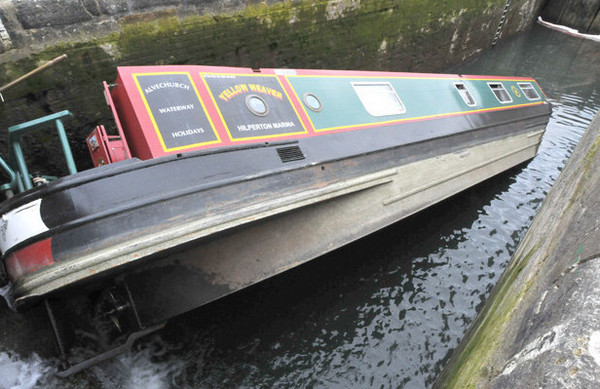 Capsized narrow boat stuck on a lock cill